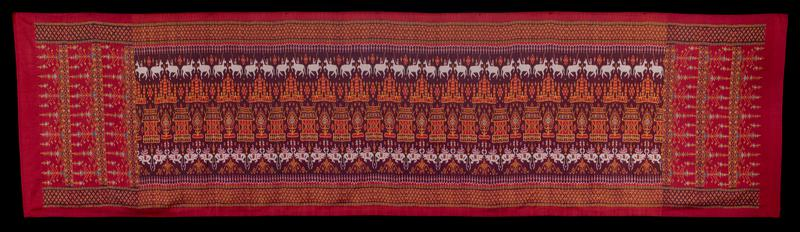 """red ground with geometric pattern in gold, green, blue and black, 6"""" wide, along edges; center section: row of llama-like creatures at top, elephants at bottom; row of temple-like structures below llamas with drum-shapes structures below temples, alternating with tree-like motifs; row of mountain shapes below elephants; not a closed tube"""