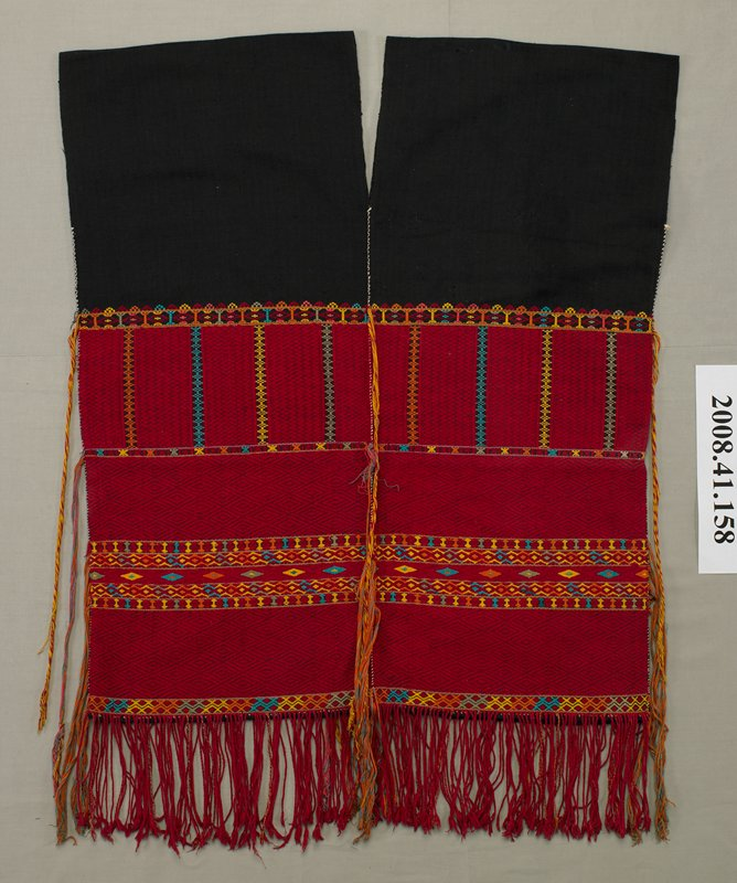 sleeveless; V neck, front and back; black fabric woven on bottom 2/3 in red with predominately diamond motifs, interspersed with orange, yellow, turquoise, khaki and pink geometric patterns; twisted red fringe at bottom; long twisted tassels of weaving threads extending down from sides and center front and back