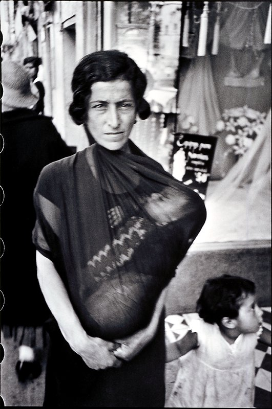 woman carrying a baby in front of her in a transparent cloth wrap, with another child at her side