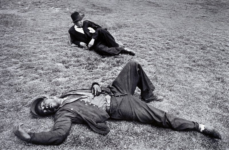 two men lying on grass, man in foreground sleeping with one leg bent upwards