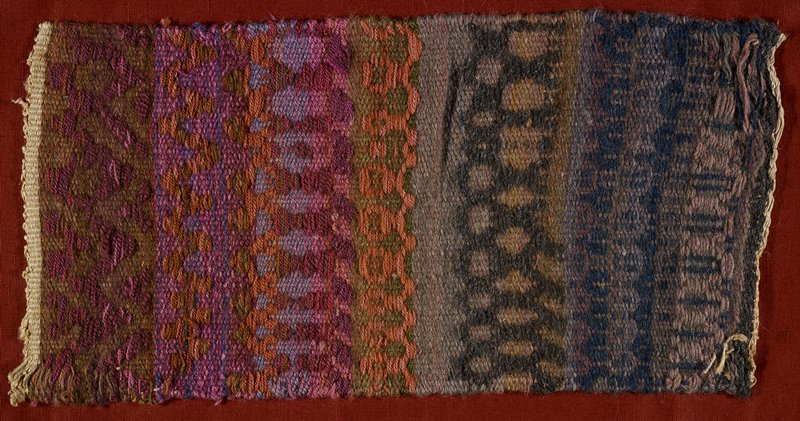 woven piece sewn to dark rust colored fabric bag (or pillowcase?); horizontal rows of weaving in purple, orange, lavender, brown, black and rust with narrow cream borders at top and bottom; geometric designs; some designs with circles and diagonals