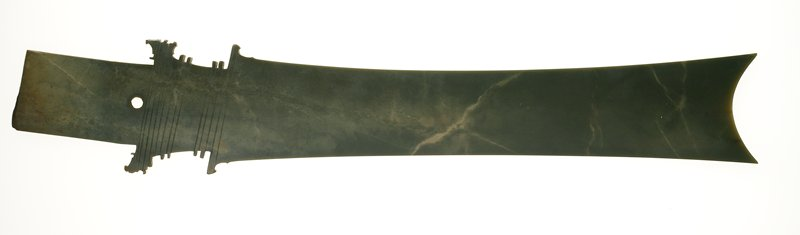 Dark olive green jade with light brown clouds. Central perforation from one side at the stem of the handle.