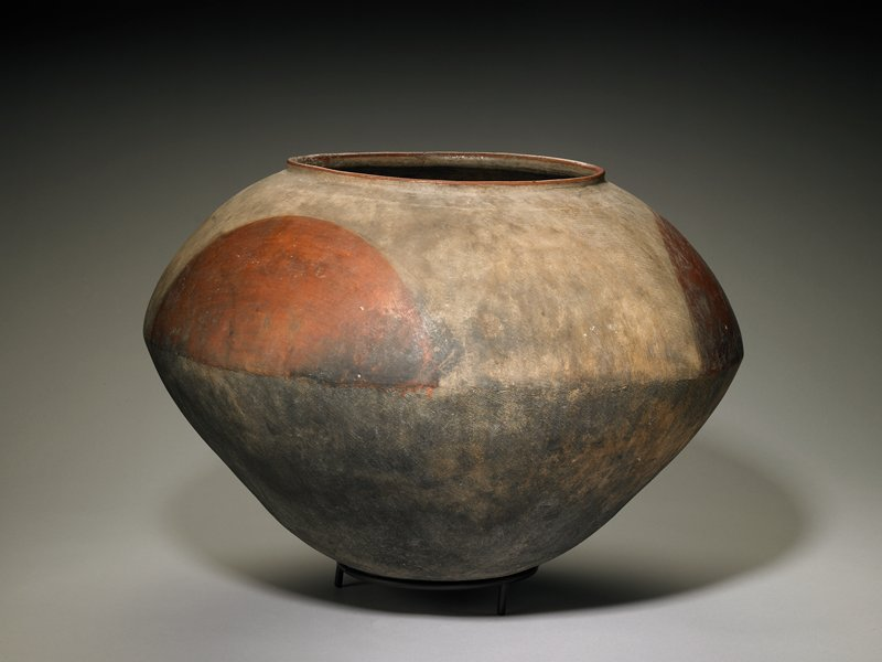 large vessel with rounded base; flaring outward to pointed shoulder and inward to slightly raised mouth rim; shades of mottled black and grey; three red-orange semicircles above shoulder