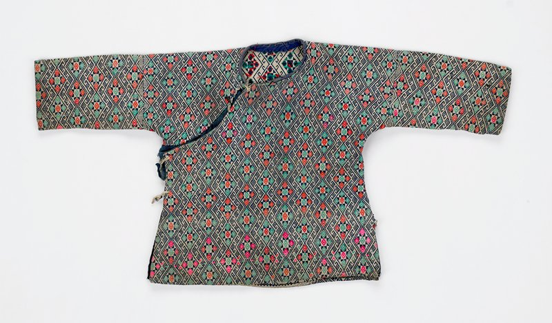 small woven jacket with navy blue, cream, green and red threads; overall design of zigzag pattern in navy blue and cream interspersed with geometric triangle and star patterns in navy blue, cream, red and green; diagonal opening from neck to armpit on PR side; lower back--same designs but green and red color only in center of geometric design; some blue diamonds and one yellow diamond across middle of back