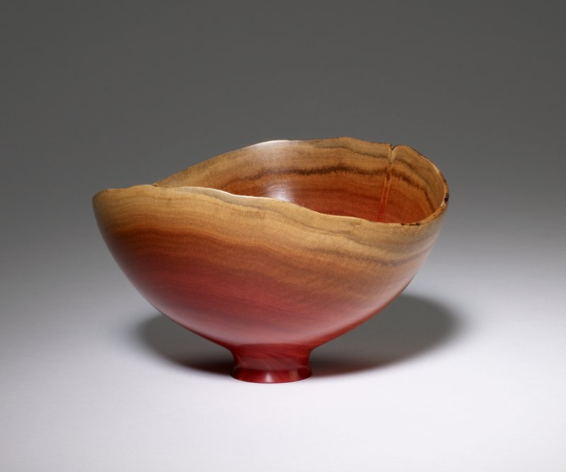 small bowl on short raised foot with flat bottom; irregular rim; pink with brown rim