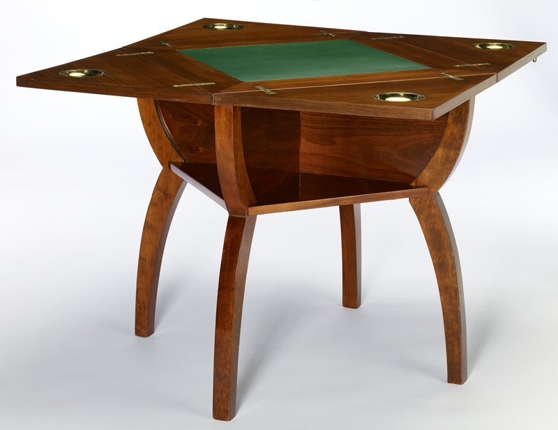 square table with leaves that fold upward creating X shape; small triangular-shaped compartment on each side of table; legs curve inward toward base of compartments/ shelves, and curve outward toward feet; four supports pull out to support leaves; green leather playing surface; small brass cup at each corner when unfolded