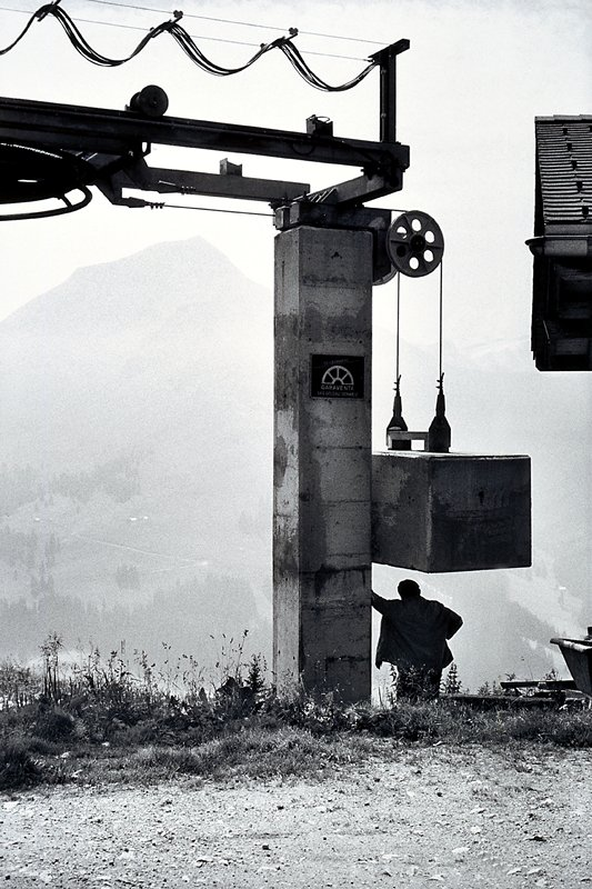 taken at a cattle fair in Switzerland; man standing under a counter weight which is part of a ski lift, in French 'un tire fesses'