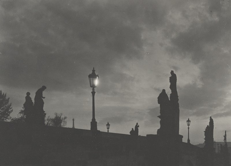 twilight or dusk with silhouettes of sculptures on bridge against sky