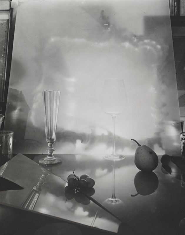 two clear glasses (pilsner glass and wine glass), pear, grapes, piece of mirror (?)