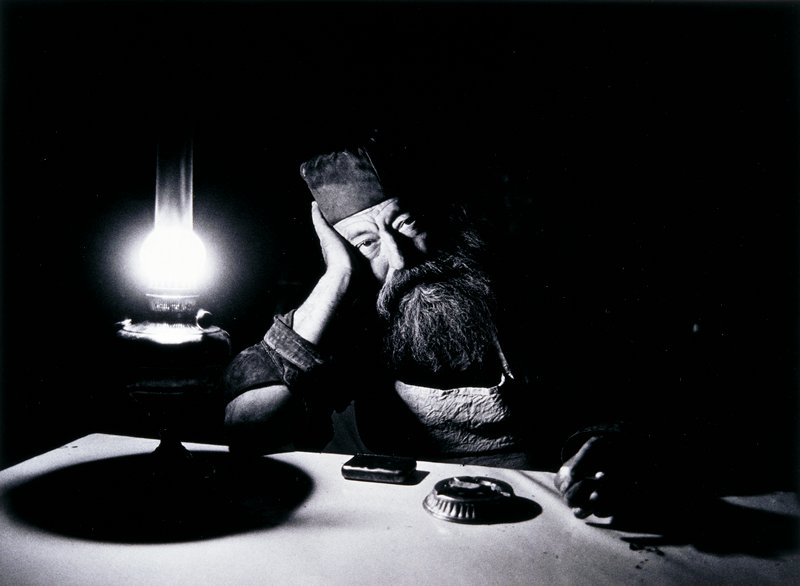 man with coarse beard wearing a cap leaning his head against his proper right hand with his elbow resting on a table; lamp to left of man's proper right arm