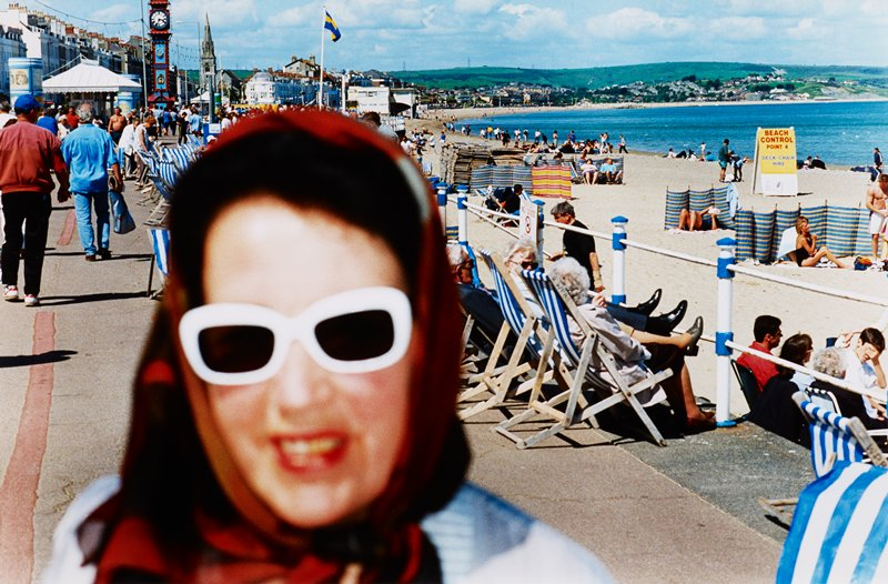 blurry woman's face, wearing white-framed sunglasses and red headscarf, in foreground L; view of a busy beach at R and paved walkway at L