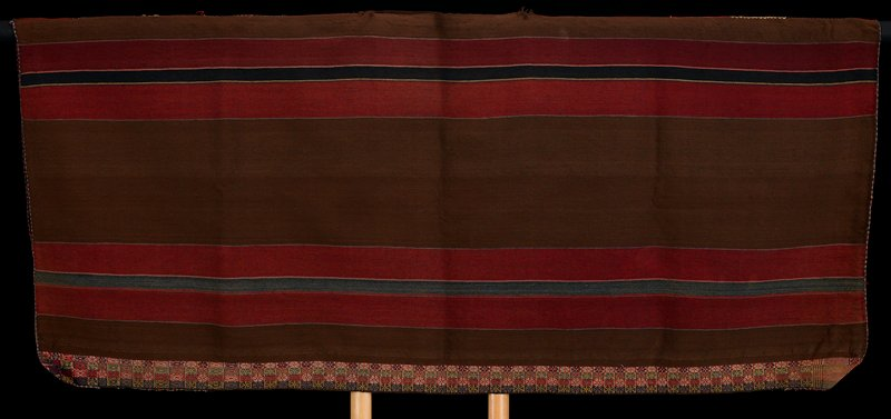 open sides; top central opening on seam for head; rust, brown and green stripes; bottom edge has four bands of multicolored flower designs; warp faced plain weave with supplementary warp weave at warp edges