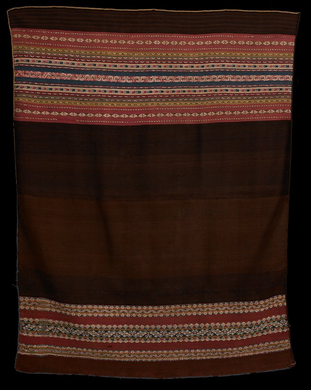 two pieces sewn together; brown, blue and tan edging; predominantly brown; one panel has three bands of multicolored patterned stripes; other panel has many patterned stripes with pink, blue, tan, green, red or purple solid stripes separating patterns; warp faced plain weave with complimentary warp patterning