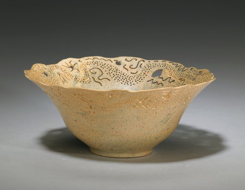rounded bowl shape, flaring outward from short foot; thin, lacey rim with pierced dots, zigzags, swirls and other organic openwork designs; yellowish-tan with red and blue spots and streaks