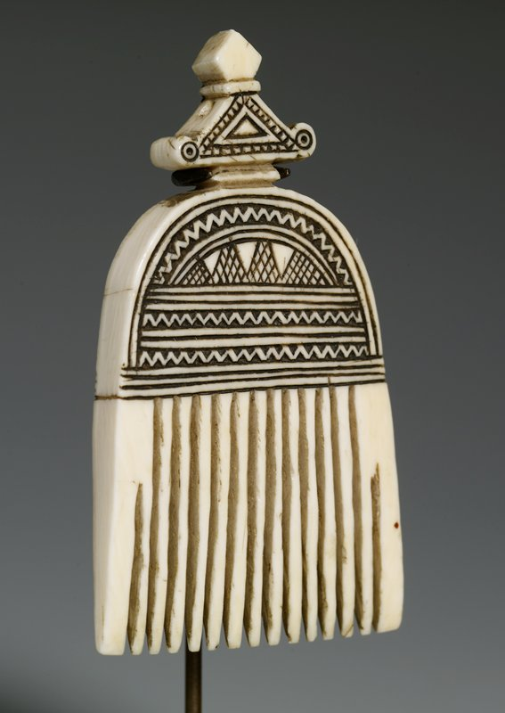 tiny comb with rounded top with finial-like protrusion; hole in top for wearing as a pendant; incised designs--same on each side--of zigzag bands, straight and curved bands and cross hatched zigzags
