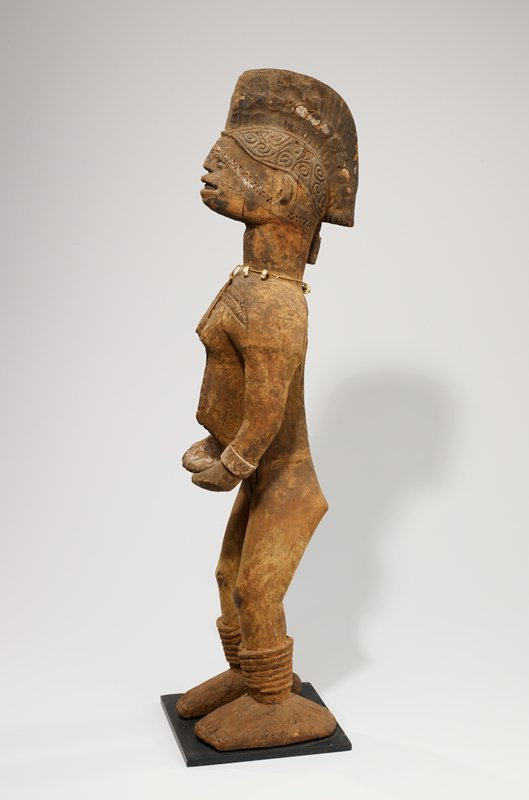 standing nude female figure with small breasts; stomach protruding at navel; very large feet; arms extending down with hands cupped upwards; very narrow face at front view, with small protruding eyes and open mouth with teeth; wedge-shaped, mohawk-like hairstyle; string necklace with four cowrie shells; cross-shaped incised zigzag designs on front and back of body; crackling, flaking patina