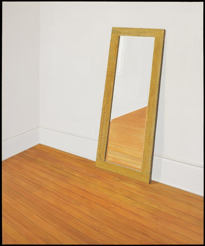 corner of white room with narrow mirror leaning against wall; hardwood floor; unframed