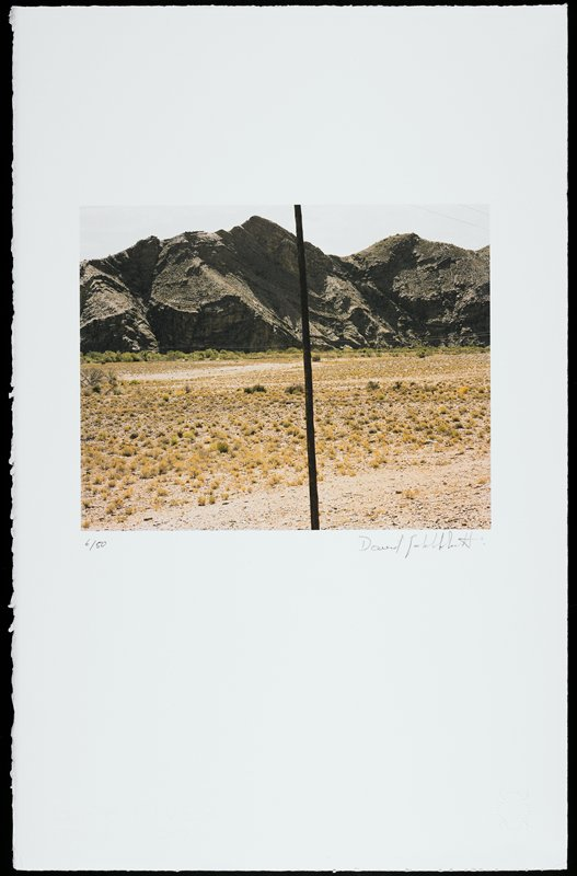 photographic image of a dry landscape with scrubby grass; grey mountains at horizon line; thin wooden pole divides center of image vertically