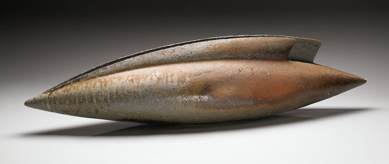 elongated eye-shaped form with slit opening in top and fin-like projection on each side of slit; grey body with golden brown and light tan drips