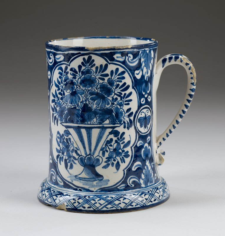 "dark blue and white tankard with flowers and abstract designs; two large vases depicted with large floral arrangements and scalloped edges; butterflies and abstract flowers between vase designs; outward flaring, rounded foot with crisscross design; large inscription with, ""IN 1728"" surrounded by decorative designs; abstract curlicue design on handle"