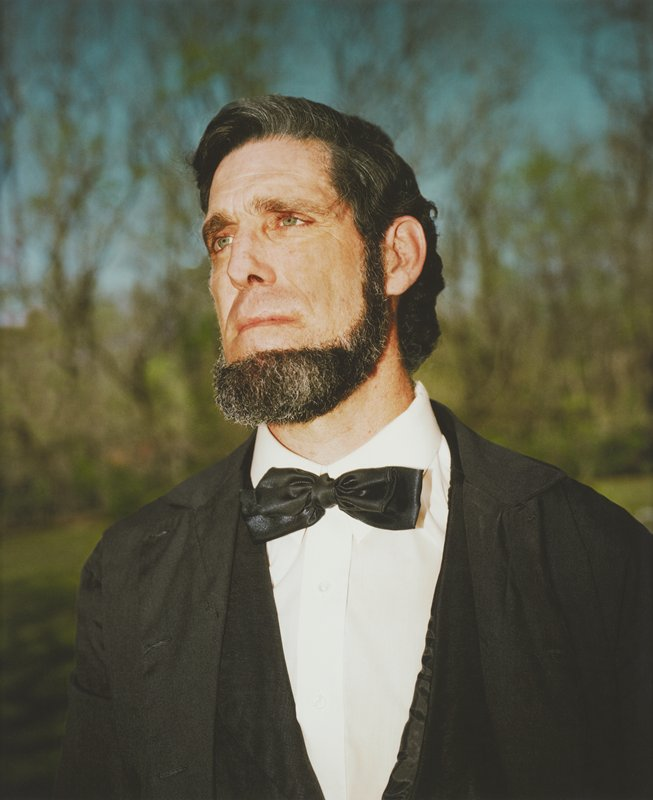 portrait of green-eyed, bearded man dressed as President Lincoln; man looking up to PR; blurry line of trees and blue sky seen through branches; framed behind glass in black wood frame; one of a set of 18 photographs to be displayed together