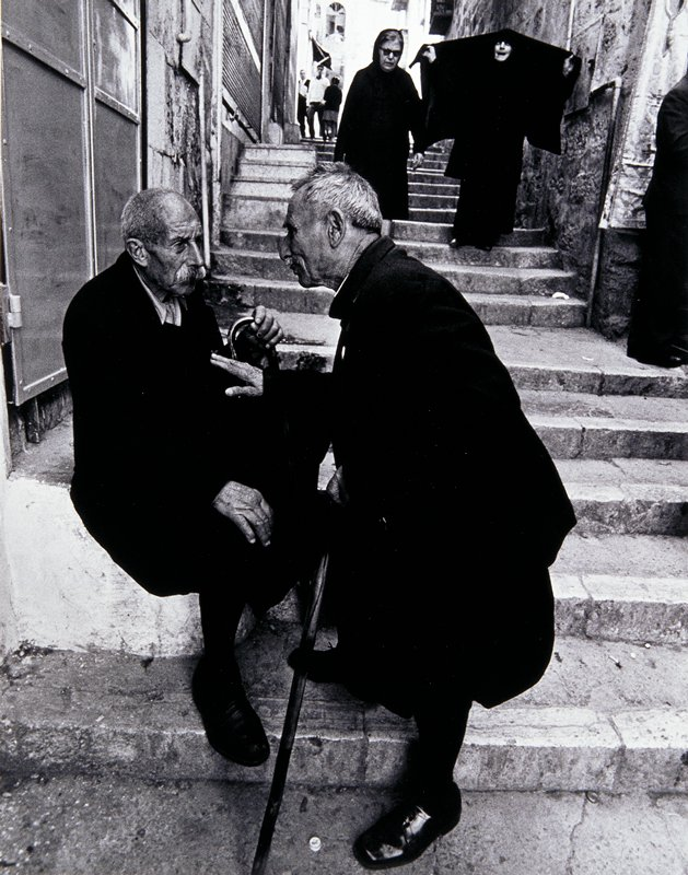 two elderly men with moustaches, dressed in black and carrying canes, on stone steps; two women in background