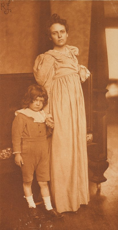 a woman and child stand in an interior space holding hands