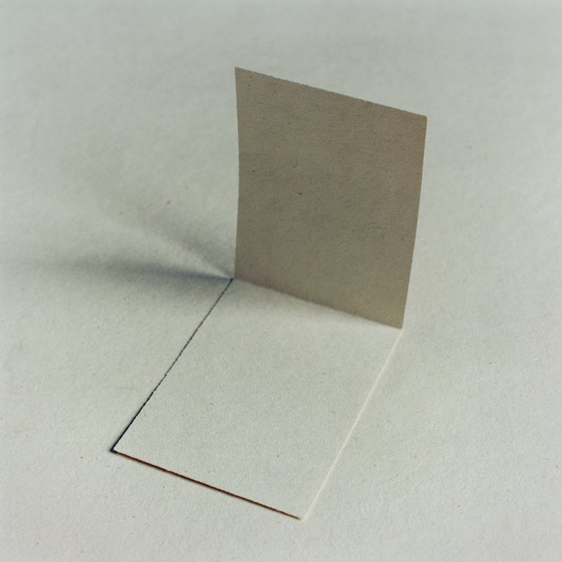 close-up image of piece of white paper with back folded up sitting atop sheet of same white paper