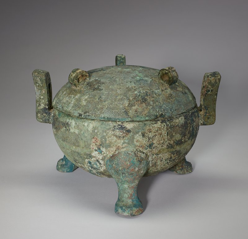 Both bowl and cover of this squat Ting are richly decorated with broad horizontal belts of various patterns broad bands of interlaced volutes and angles, granulation and striation, as well as T'ao-t'ieh masks placed upside down. The sides of the bent handles are incised with volutes, the face of the handles with volutes and angles. The knees of the short, thick legs are adorned with t'ao-t'ieh-like masks. Three upright disks with flat, truncated projections at the top are affixed to the lid, which has a central medallion with a border of volutes and angles framing a wide band of Huai heart-shaped blades. The low, rounded bottom of the bowl suggests Kin-ts'un as the possible provenance of this vessel. Patina grayed green with areas of sharp green.