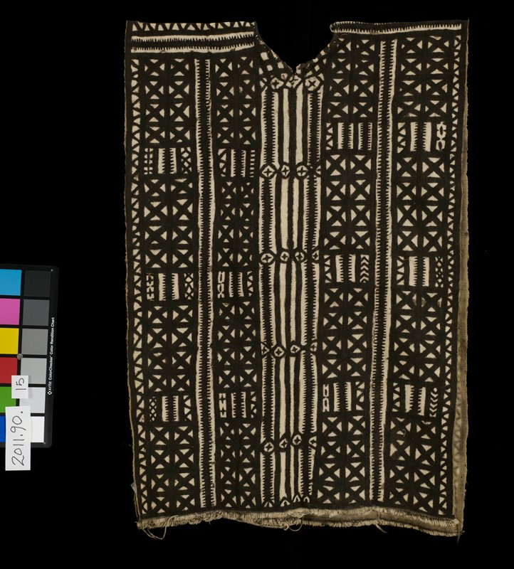 black and cream abstract design; 4 panel (mud cloth) shirt; horizontal design across shoulders; vertical design on body of the shirt; short fringe across bottom; very small vee at front of neckline