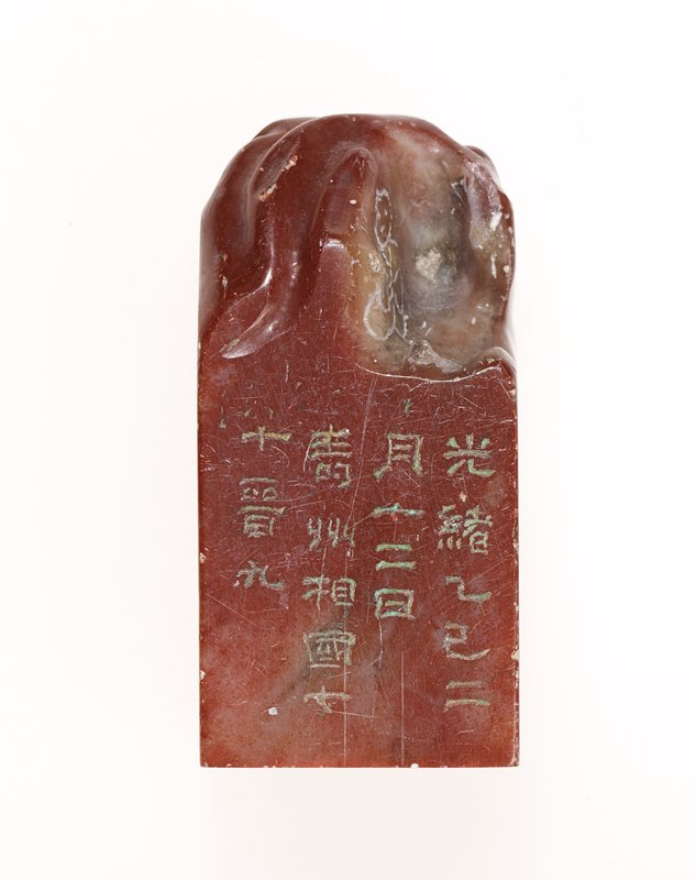 red stone with milky-colored swirls; roughly-carved top with open area at one corner with incised seated figure; incised inscriptions on two sides as well as stamp surface on bottom