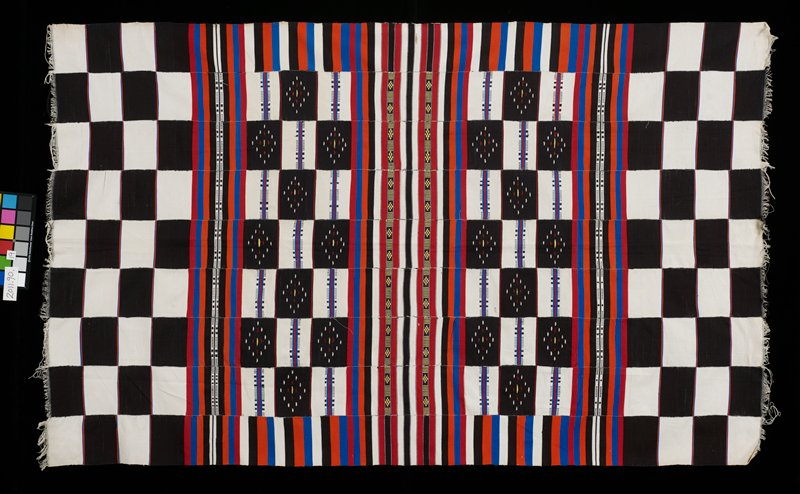 nine paneled wrap with 4 rows of black and white squares at each end; middle section - red, blue, orange, black and white stripes and some black and white abstract designs; short, narrow fringe at each end; at center: bands of black and yellow