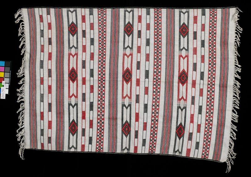 white fabric skirt with red and black embroidery in large diamond designs and abstract patterns; black and white fringe