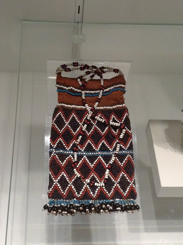 rectangular brown pouch; beaded overall with repeating diamond bands in red and white with blue and white horizontal center band and black beads on ground; blue and white beaded bands at top; beaded tassels at bottom of blue, black and white; strap beaded with black, red and white beads; received mounted with Plexi cover
