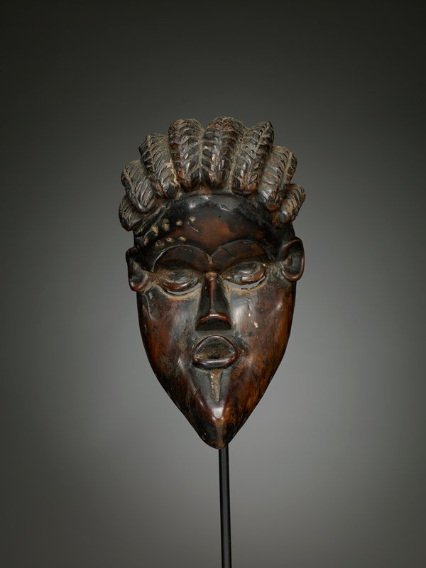 human face mask; curved, concave at eyes, forming crescent shape profile; hair in rows of thick braids; eyes partially closed; long nose; protruding lips; mottled, waxy patina
