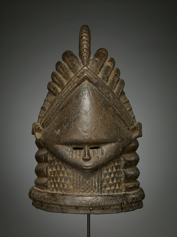 very small, teardrop-shaped face; small features--small slit eyes; deep vertical lines beneath eyes on each cheek; triangular incised patterns under chin; ribbed rings around neck; geometric deeply-carved hairstyle or hat, with arc on top of head and triangular patterns on sides of head; thick horizontal band of triangles behind head from ear to ear; medium to dark brown patina