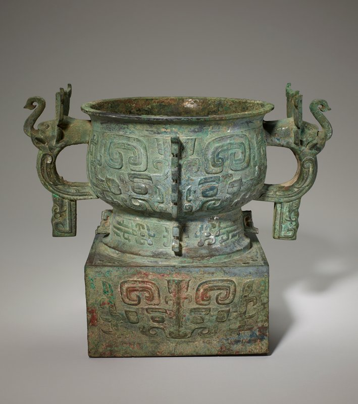 Several aspects of this vessel set it apart from others of the Kuei type in the collection. Most immediately arresting is the high, square base on which it rests. Other differences are the spiral ground of the decor, the absence of a neck belt, the division of the vessel into four vertical panels by four flanges in the foot belt by two flanges and the two handles on the belly. Atypical Early Chou feature distinguishes the heavy, thick flanges the breaking through of the T-scores to give the impression of big hooks. The flanges on the body form the center lines of the familiar bodied t'ao-t'ieh. In the foot belt just below, the flanges are the median lines of rudimentary t'oa-t'ieh masks (nose and forehead shield) flanked by trunked dragons of the winged variety which are hee drawn so far apart as to isolate and emphasize the t'ao-t'ieh shield. The t'ao-t'ieh on the base is the same as the one on the belly except for the central line, here a slight ridge instead of a flange. The handle is the most remarkable feature of the vessel. The bow displays the wings of a bird in relief, and the projection at the bottom contains the curved-up bird's tail and its feet descending almost to rest on the tail. The head of the bird body is that of an elephant with big ears in pointed C-shape, raised trunk and protruding tusks. Patina green