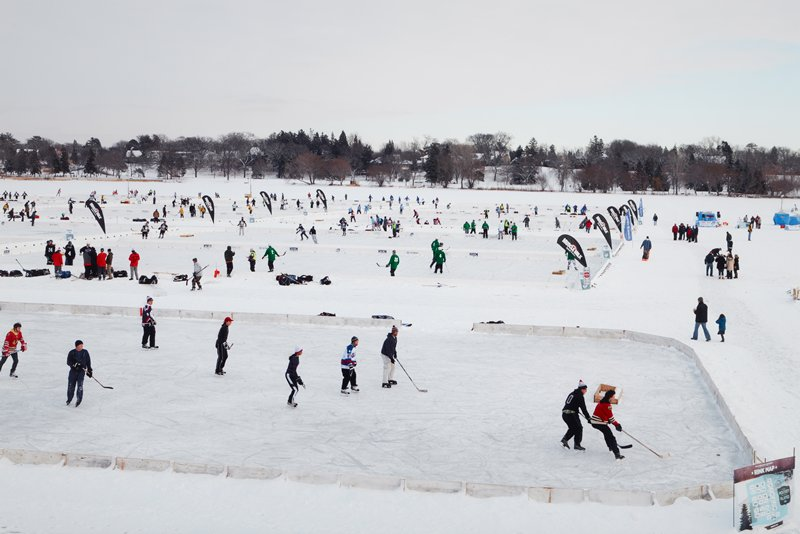 LON139180; caption: USA. Minnesota. Minneapolis. Winter Games. Pond Hockey. 2012.; color image of multiple ice rinks on frozen lake; figures playing hockey in each rink; trees and houses in distance; light grey and blue sky