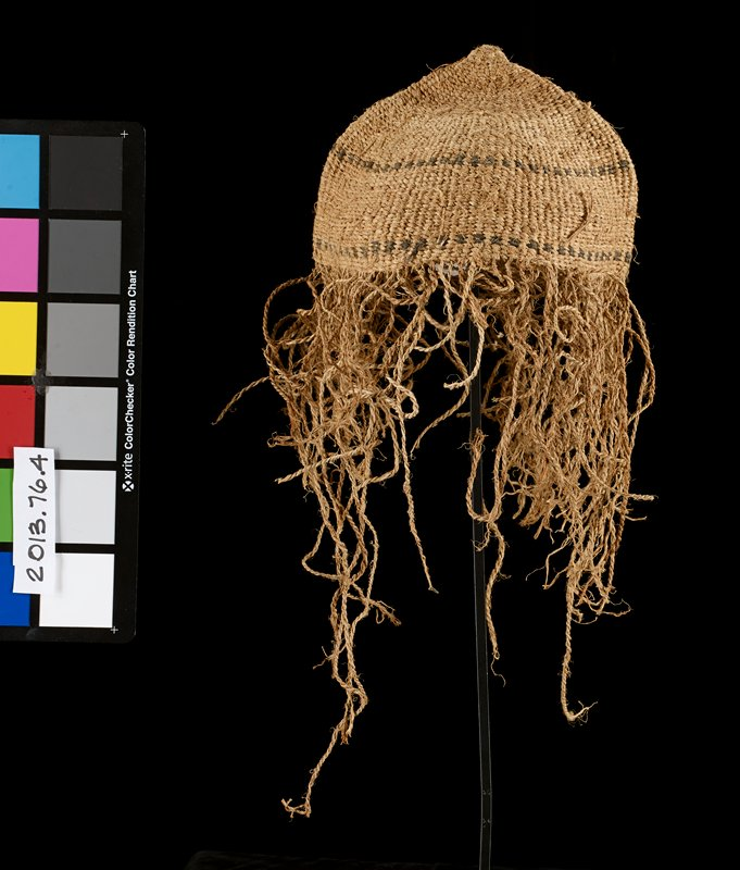 natural tan hat with long tan tasseled fringe around brim; two black stripes circle cap; round in shape