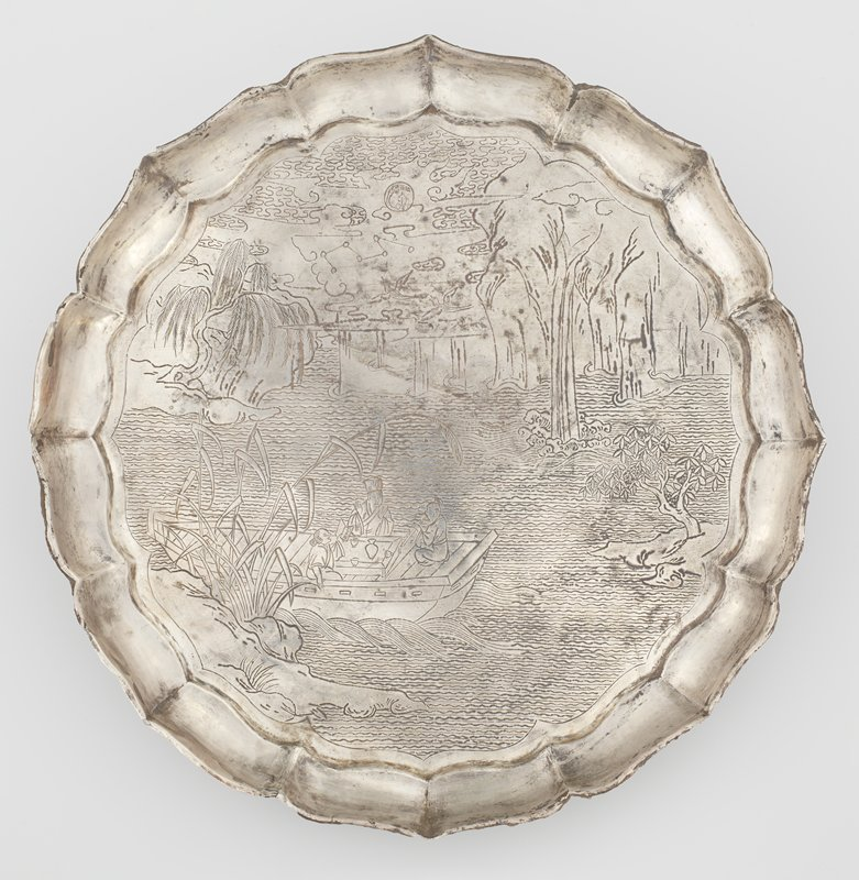 "chased silver dish decorated with scene from the ""Former Red Cliff Ode"" by Su Shi (1037-1101); engraved in painterly baimiao style showing the poet in court robes with two companions relaxing in a boat drifting on tranquil water, with a winepot and cups on the table in front of them; one figure playing a flute and the other holding an open book; rocky banks with grasses and tall reeds, a willow and a cassia tree; small waterfall spilling down from high cliffs at the far shore; sky with pair of birds flying to the left towards a constellation of seven stars drawn as circles joined by thin lines to form the Big Dipper seen through drifting clouds surrounding a full moon engraved with the legendary yu tu dao yaou scene of the Moon Rabbit under the cassia tree pounding a pestle in a mortar; shallow plain sides of octafoil bracket-lobed outline rising to a barbed everted rim"