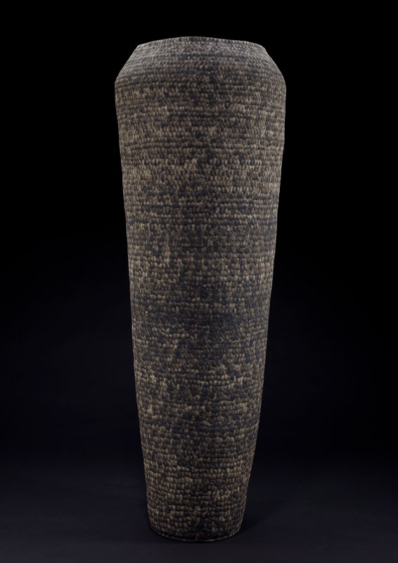 off-white stoneware body with decoration on exterior of horizontal rows of black smoky drip-like spots, creating a coil-like effect; tall form with flat base, flaring outward to slightly wider shoulder, and in to wide mouth; slightly irregular circumference
