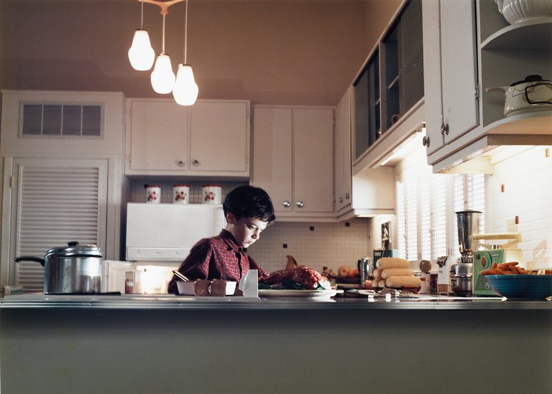 boy with brown hair wearing a patterned maroon shirt seen behind a counter in a kitchen with white cabinets; ham on a plate and a stack of ears of corn on counters