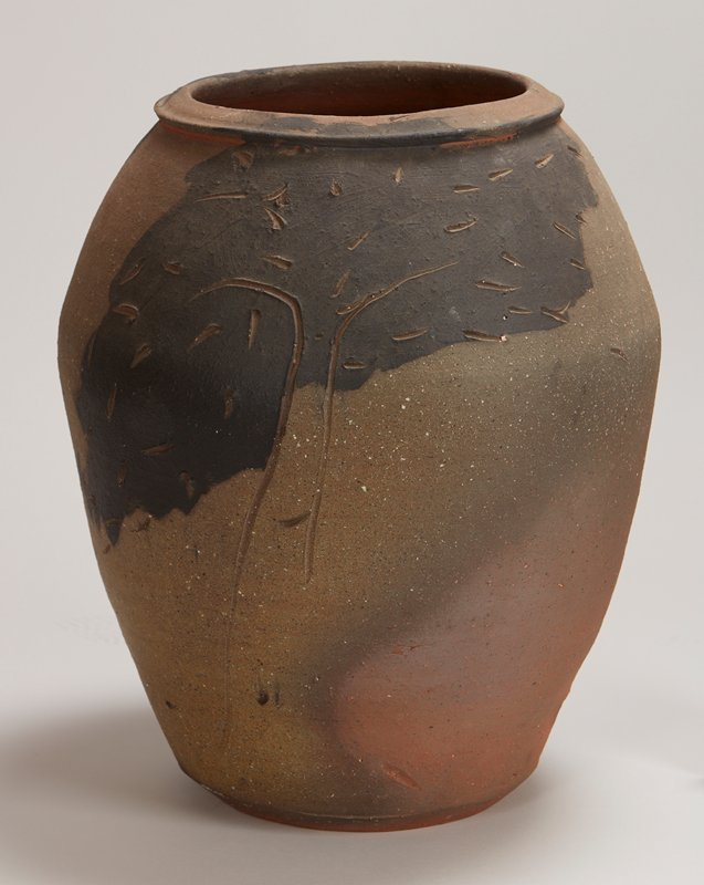 brown, rough-textured, large jar with broad areas brushed with black slip; scattered short and linear marks carved in clay