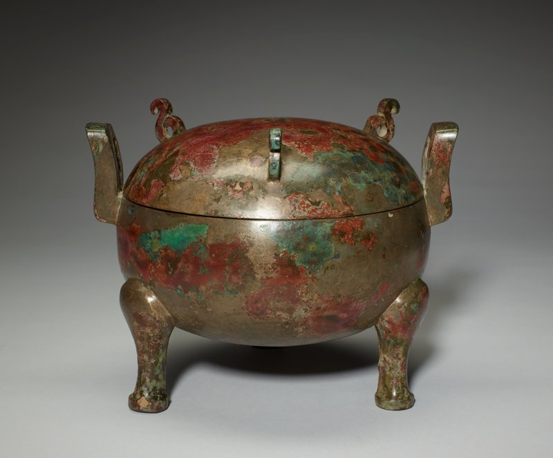 round body on tall tripod legs with flat feet; pair of U-shaped handles; domed cover with three decorative scrolls; copper-colored, red and green mottled patina