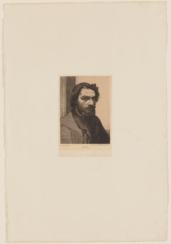 portrait of a man with short, curly dark hair and a dark beard and moustache; door behind man in ULQ