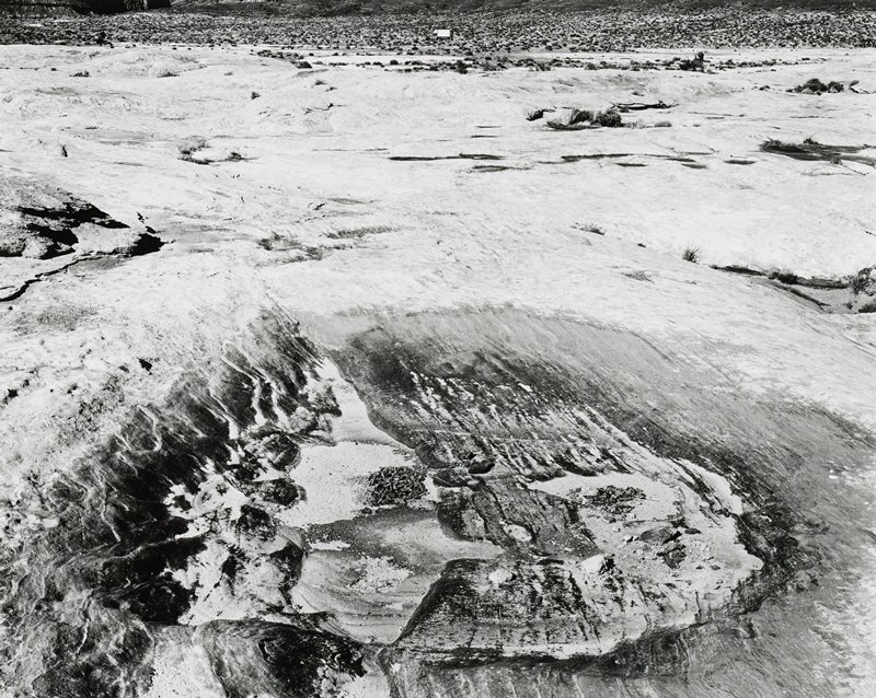 crater-like rock formation in foreground center; truck with white topper at top center