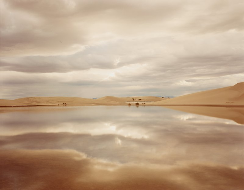reflections of clouds on body of water in landscape with low sandy hills; horizon line near center of image