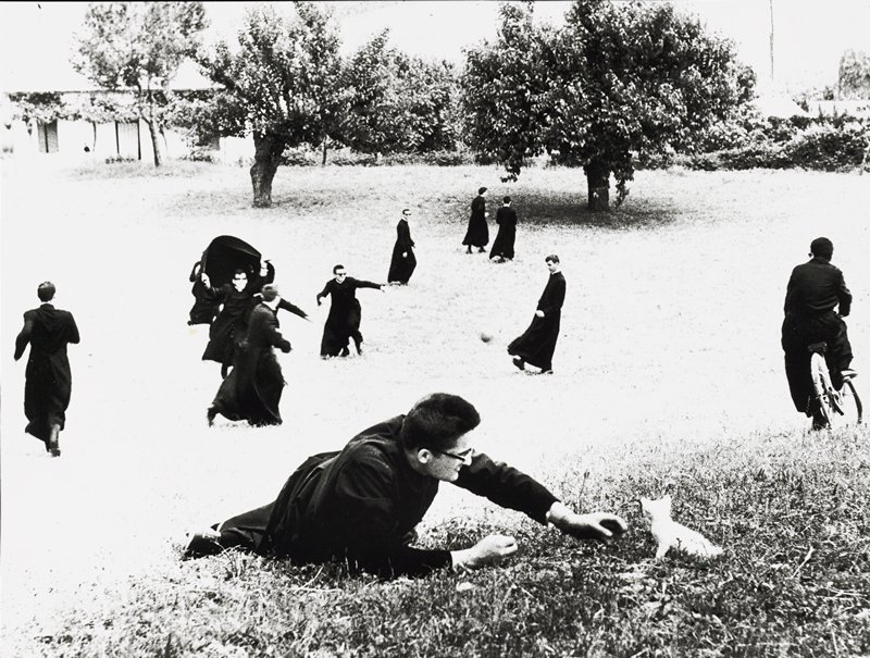 young priests in an open field with trees in background; group playing soccer at center; figure at right riding a bike; priest in foreground playing with a kitten