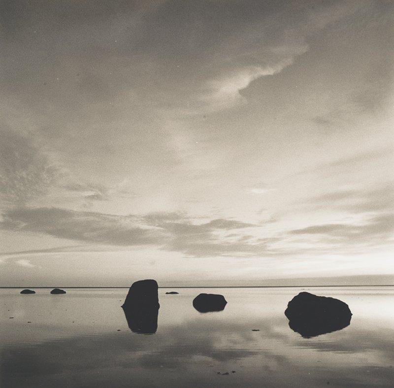 dark rocks in calm, reflective water; clouds in sky