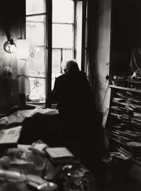 cluttered room with papers in cubbyholes at left and book and papers on table, LLC; old man seen from back in front of window at center